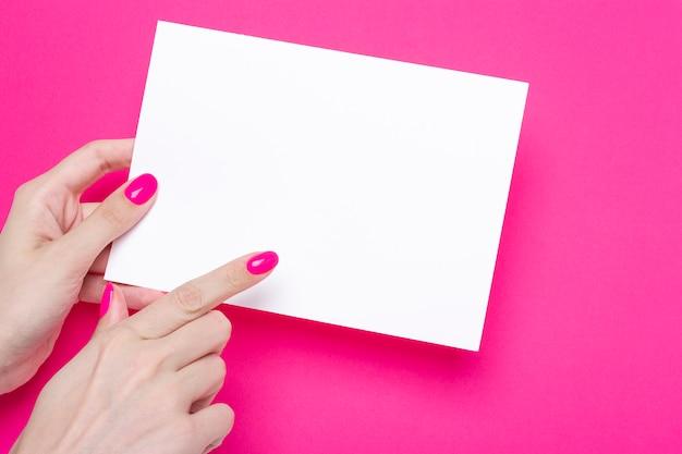 Mano femenina sostiene un cartel a5 hoja en blanco sobre fondo rosa