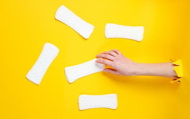 La mano femenina sostiene la compresa sanitaria diaria a través del agujero rasgado de papel amarillo. concepto de moda minimalista