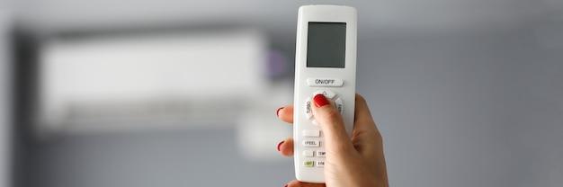 Mano femenina sostiene el control remoto para primer plano de aire acondicionado. establece la temperatura de confort del concepto de acondicionador.