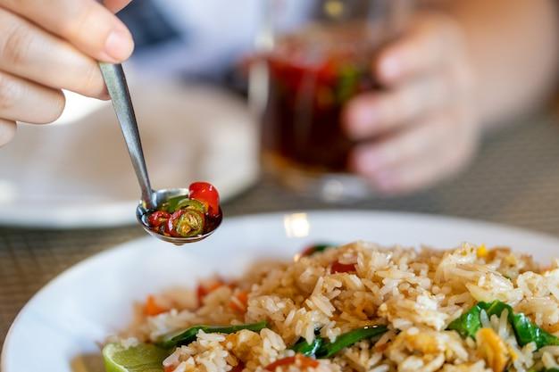Mano femenina sostiene una cuchara de metal con condimento de pimiento rojo y verde, primer plano, en el fondo de arroz y un vaso.