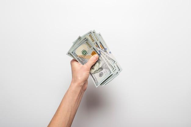 La mano femenina sostiene, cuenta dinero, dólares en un fondo claro. concepto de pago, riqueza, compra, impuestos.