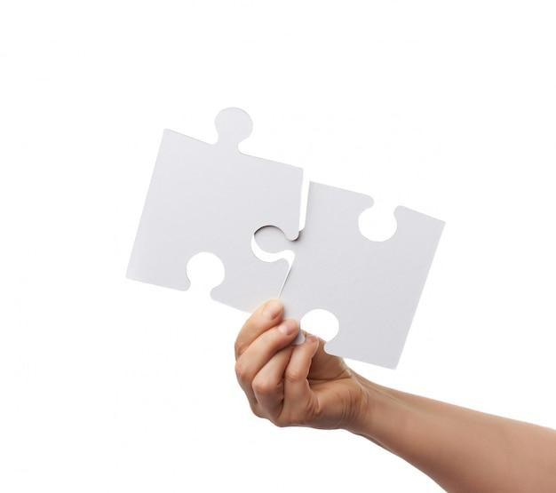 Mano femenina sostiene dos grandes rompecabezas de papel blanco vacío aislado sobre fondo blanco.