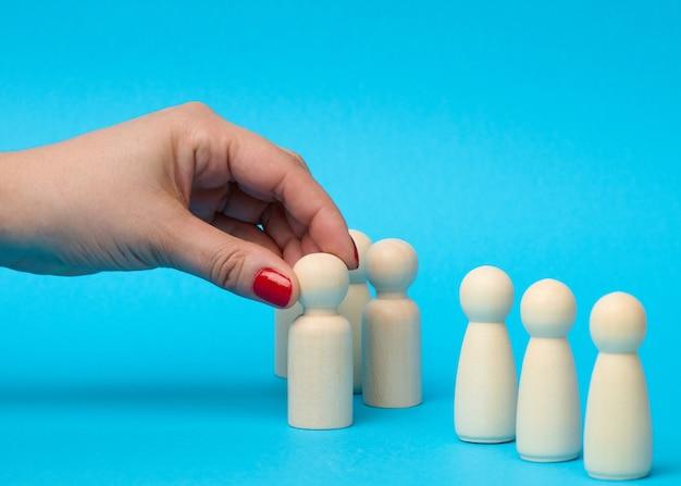 Una mano femenina sostiene una figura de madera elegida entre la multitud. el concepto de encontrar empleados talentosos, gerentes, crecimiento profesional. contratación de personal, de cerca