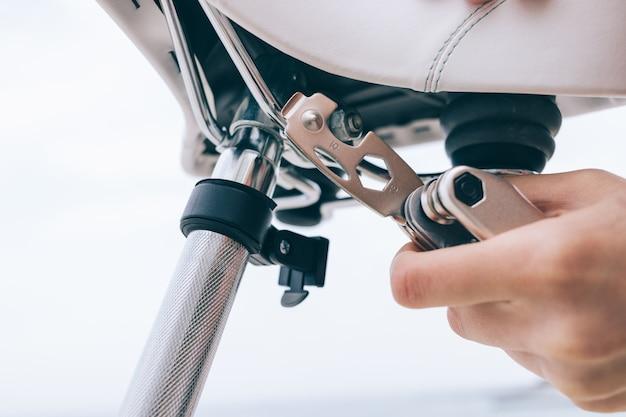 Mano femenina sostiene una herramienta para reparar una bicicleta