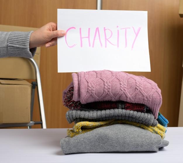 Mano femenina sostiene una hoja de papel con una caridad de inscripción y una pila de ropa, el concepto de asistencia y voluntariado. clasificando cosas