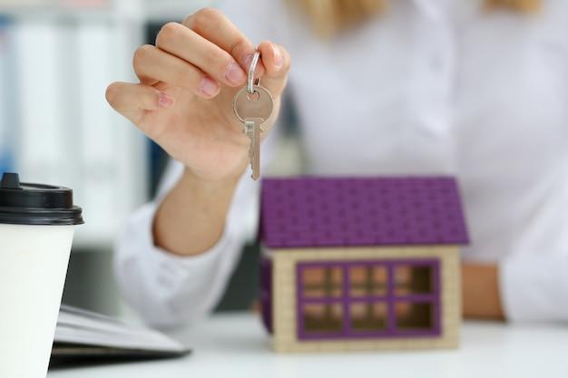 Mano femenina sostiene la llave de la cerradura en la mano