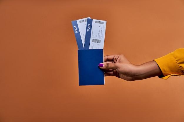 La mano femenina sostiene un pasaporte azul con dos boletos. concepto de viaje