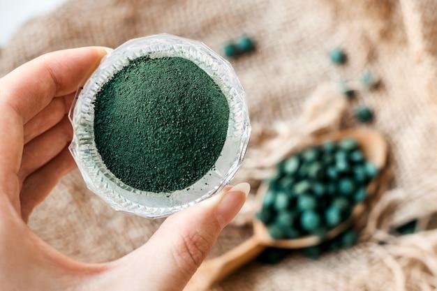 Mano femenina sostiene polvo de espirulina sobre un fondo de arpillera y una cuchara con tabletas de algas verdes