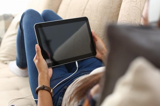 Mano femenina sostiene tableta en casa mientras