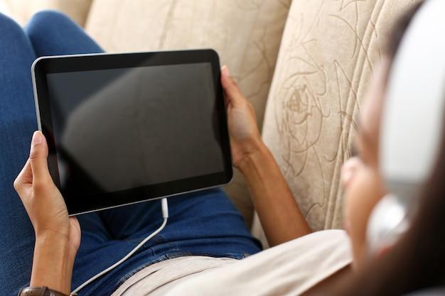 Mano femenina sostiene tableta en casa