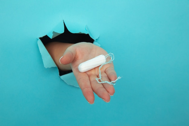 Mano femenina sostiene tampón de algodón a través de primer plano de fondo de papel rasgado, concepto de atención médica