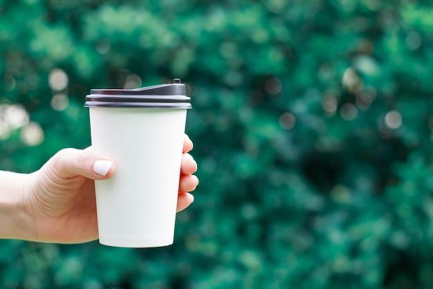 Mano femenina sostiene la taza de café de papel