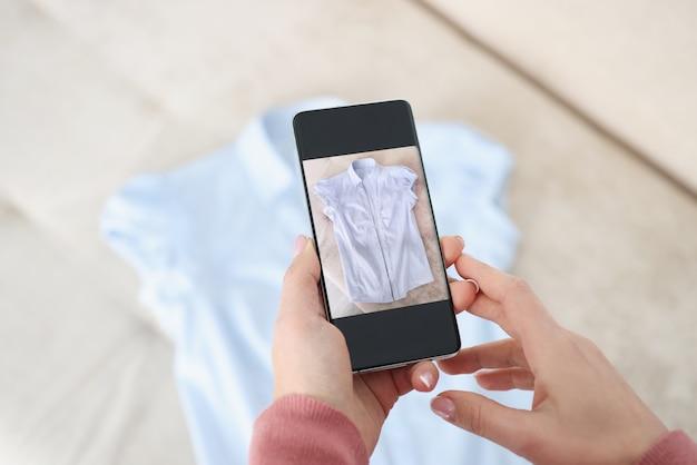 Mano femenina sostiene teléfono inteligente y hace fotos de camisa azul