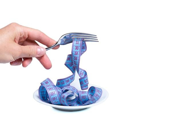 Mano femenina sostiene un tenedor con cinta métrica enrollada sobre un plato vacío aislado en blanco