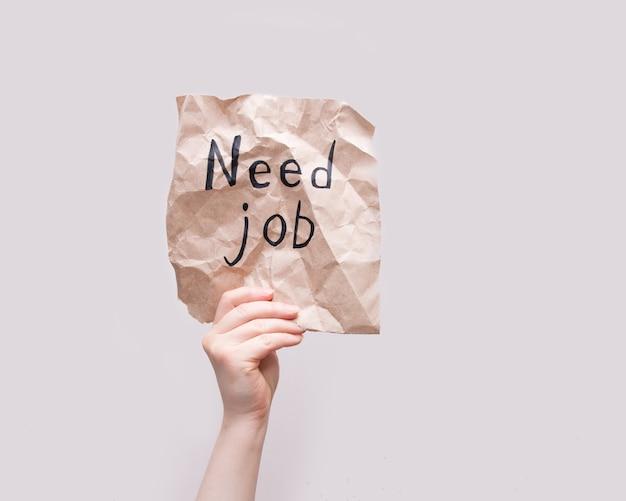 Mano femenina sostiene un trozo arrugado de papel de regalo marrón con la inscripción necesita trabajo