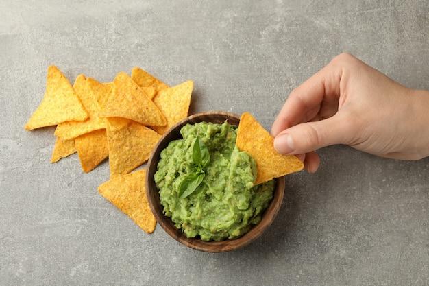 Mano femenina sumerge la rebanada de chips en guacamole, vista superior