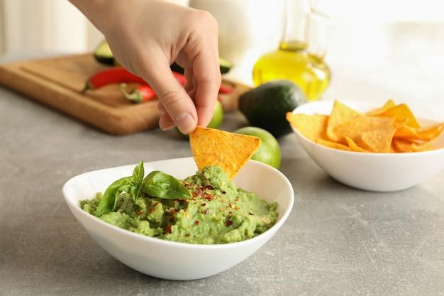 Mano femenina sumerge una rodaja de chips en guacamole