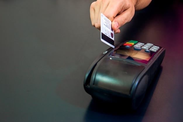 Mano femenina con tarjeta de crédito y terminal de banco, máquina de tarjeta o pos terminal con tarjeta de crédito blanco en blanco insertado aislado en fondo negro