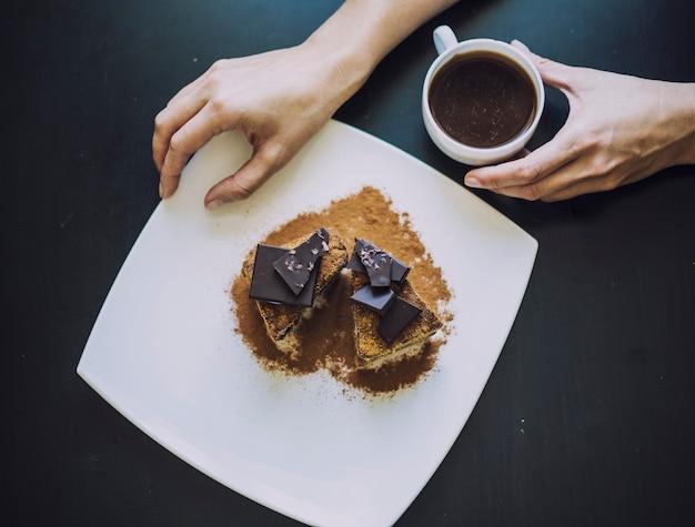 Mano femenina con una taza de café y un hermoso primer plano de pastel de chocolate sobre la mesa