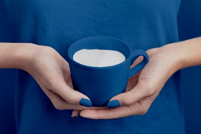 Mano femenina con taza de leche del color del año