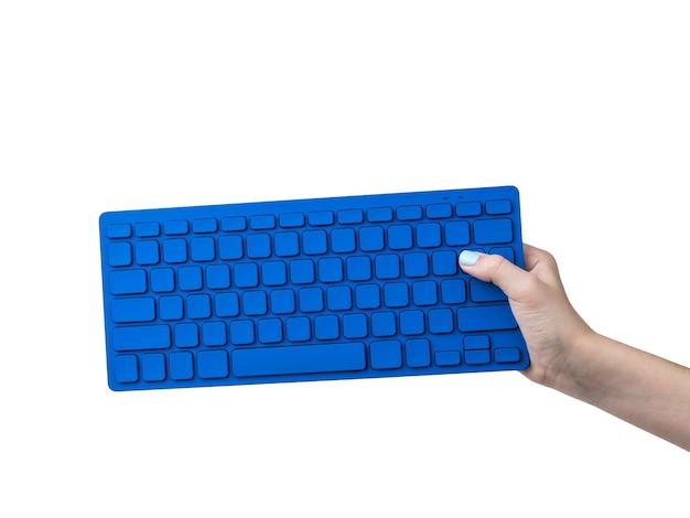 Mano femenina con teclado azul aislado en blanco. equipo de oficina.