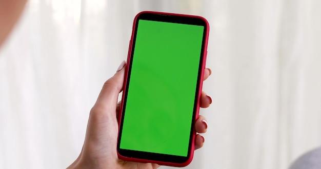 Mano femenina con un teléfono inteligente con una pantalla verde sobre blanco