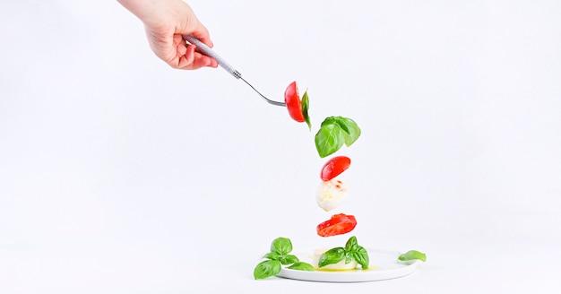 Mano femenina con tenedor y ensalada voladora en marco. ensalada caprese italiana tradicional. tomates, mozzarella, albahaca, aceite de oliva copia espacio