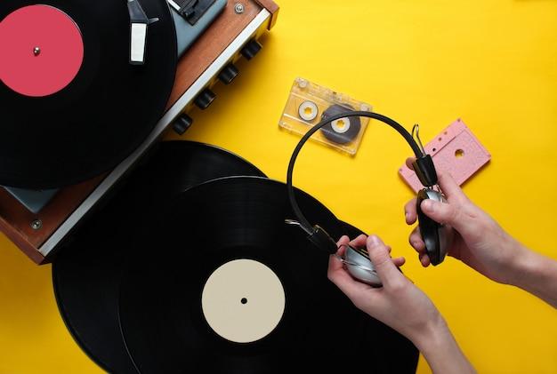 Mano femenina tiene auriculares. estilo años 80 reproductor de vinilo, cinta de audio sobre fondo amarillo. vista superior, endecha plana