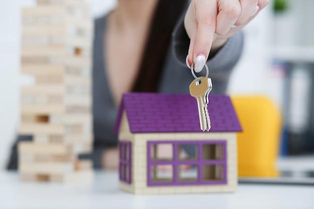 La mano femenina tiene la llave de la cerradura en la mano contra el telón de fondo de los servicios inmobiliarios del concepto de alquiler de compra venta de casa de juguete en el mercado.