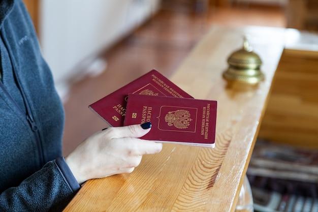 Mano femenina tiene pasaporte ruso en el mostrador de recepción de madera