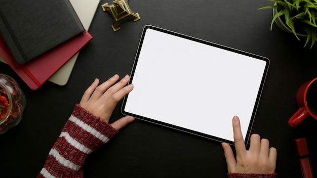 Mano femenina tocando en tableta digital en mesa de trabajo elegante femenino con suministros y decoraciones