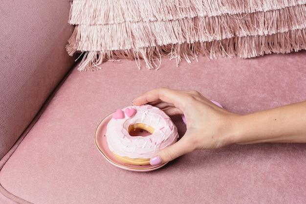 Mano femenina toma una rosquilla dulce rosa sobre una superficie rosa