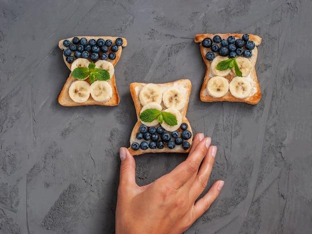 Mano femenina toma un sándwich casero con queso cottage, arándanos, plátano, menta