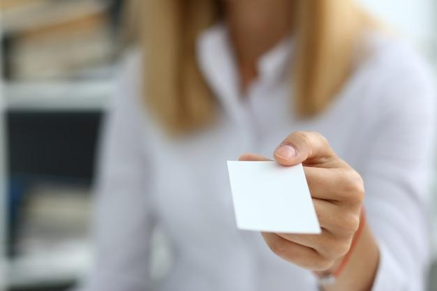 Mano femenina en traje dando tarjeta en blanco