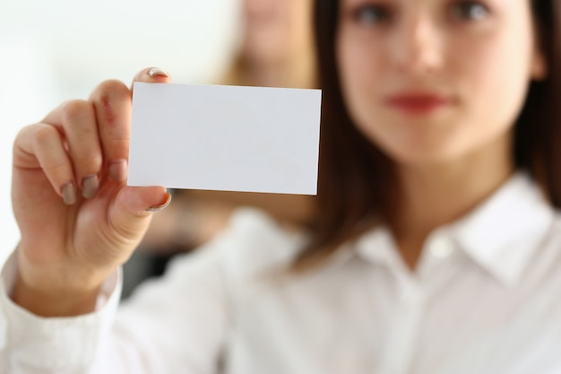 Mano femenina en traje dar tarjeta de visita en blanco al visitante