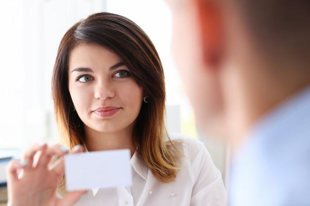 Mano femenina en traje dar tarjeta de visita en blanco a hembra