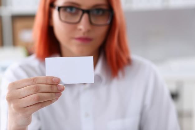 Mano femenina en traje dar tarjeta de visita en blanco