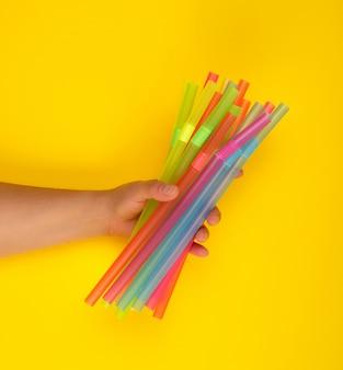 Mano femenina con tubos de cóctel de plástico multicolor