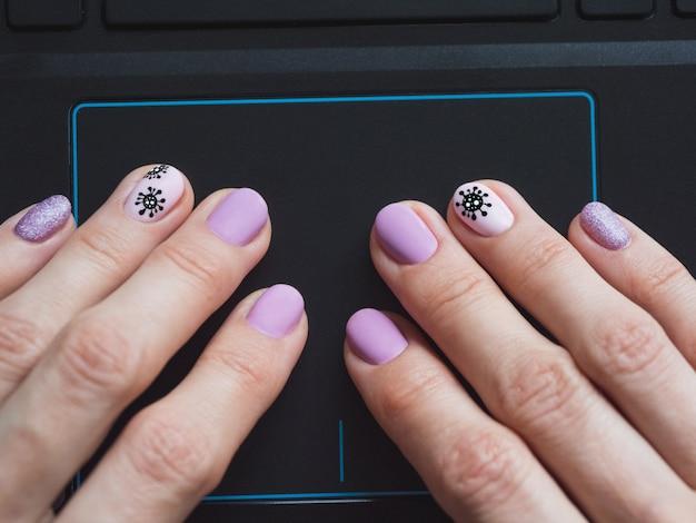 La mano femenina está usando un panel táctil en un cierre de la computadora portátil para arriba. manicura creativa sobre el tema del coronavirus.