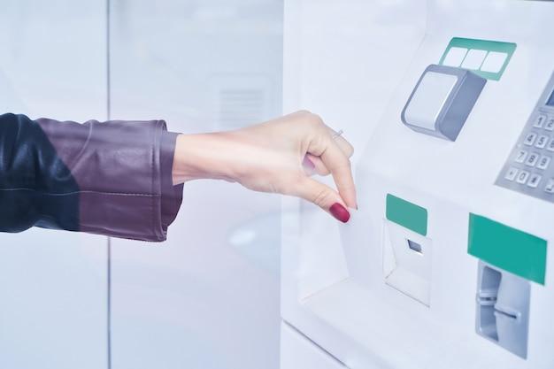 Mano femenina utiliza pago sin contacto con tarjeta de crédito para retirar dinero del cajero automático