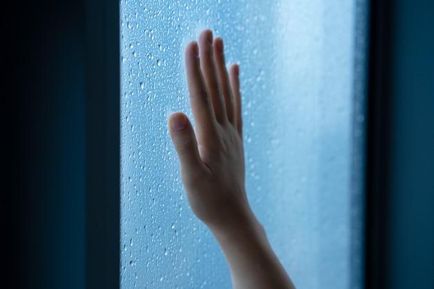 Mano femenina en la ventana durante la lluvia. vaso en gotas de agua.