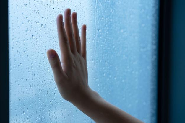 Mano femenina en la ventana durante la lluvia.