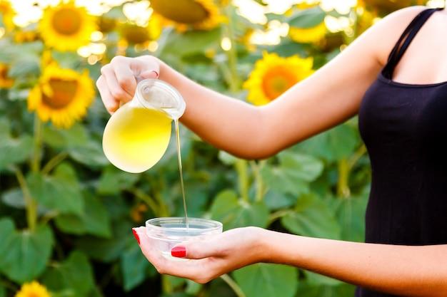 La mano femenina vierte el aceite de girasol de un jarro en un cuenco en un campo del fondo. concepto de cosecha