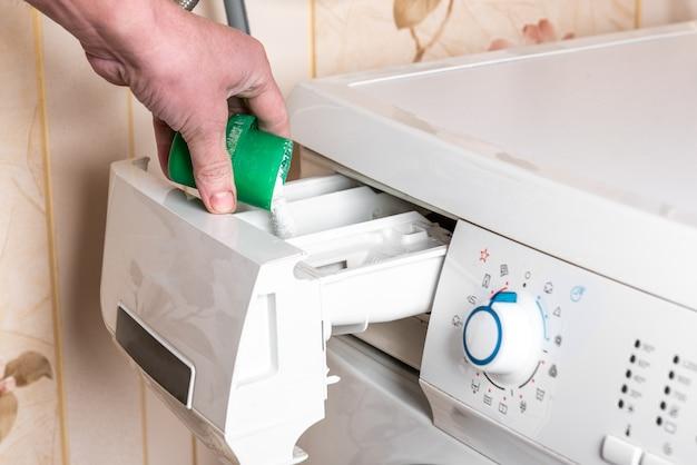 Mano femenina vierte el detergente en polvo en la lavadora