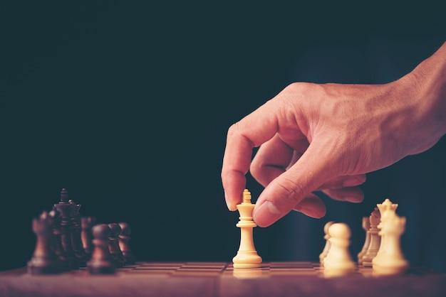 Mano de la figura móvil del ajedrez del hombre de negocios en juego del éxito de la competencia. estrategia