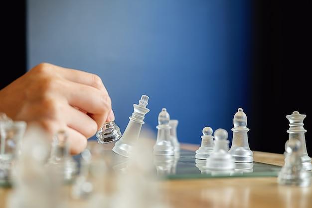 La mano de la figura móvil del ajedrez del negocio en el éxito de la competencia juega. concepto de gestion