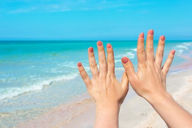 Mano firme sobre mar azul y cielo, viajes de verano, vacaciones