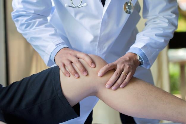 Mano del fisioterapeuta dando ejercicio de rodilla al paciente masculino en la clínica
