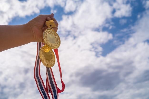 Mano ganadora levantada sosteniendo dos medallas de oro con cinta tailandesa contra el cielo azul.