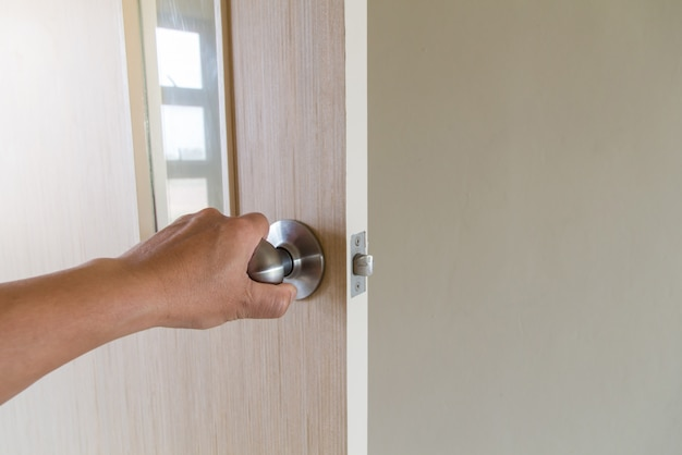 La mano de la gente abre la puerta hacia adentro, la puerta exterior se abre y la puerta de entrada
